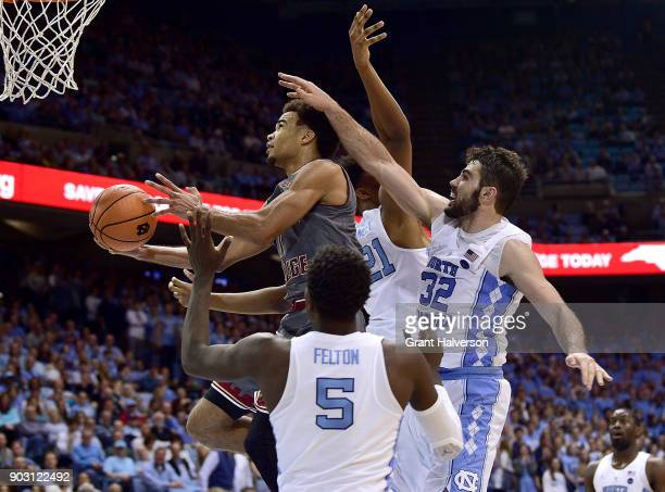 Jerome Robinson of the Boston College Eagles drives between Luke Maye and Jalek Felton of the North Carolina Tar Heels during their game at the Dean...