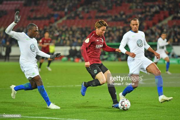 Jerome Roussillon and John Anthony Brooks of Wolfsburg tackle Takuma Asano of Hannover during the DFB Cup match between Hannover 96 and VfL Wolfsburg...