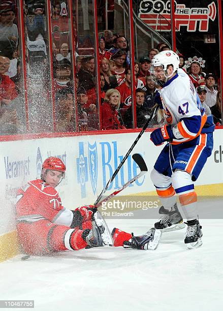 Jerome Samson of the Carolina Hurricanes slides into the boards as Andrew MacDonald of the New York Islanders pursues the puck during an NHL game on...