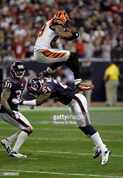 Jerome Simpson of the Cincinnati Bengals leaps over Brice McCain of the Houston Texans as he runs for yards after they catch in the second half...