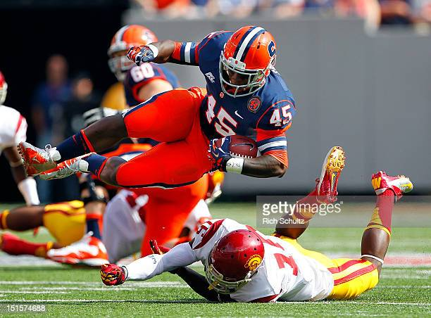 Jerome Smith of the Syracuse Orange is takled by Anthony Brown of the USC Trojans during a game at MetLife Stadium on September 8, 2012 in East...