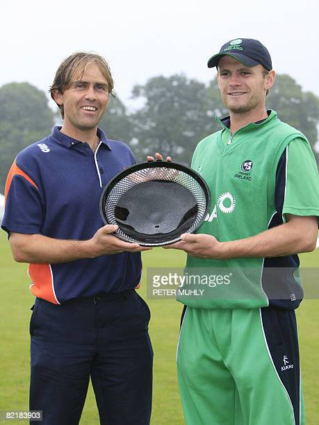 Jerome Smits captain of the Dutch cricket team and William Porterfield captain of Ireland pose for photographs with the qualifying trophy after the...