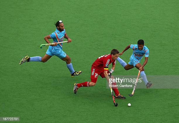 Jerome Truyens of Belgium is chased by his opponents during the match between India and Belgium on day four of the 2012 Champions Trophy at the State...