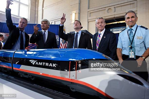 Jerome Wallut , President of Alstom Transportation Inc., an others call people over for a photo with a scale model after an event to unveil a new...