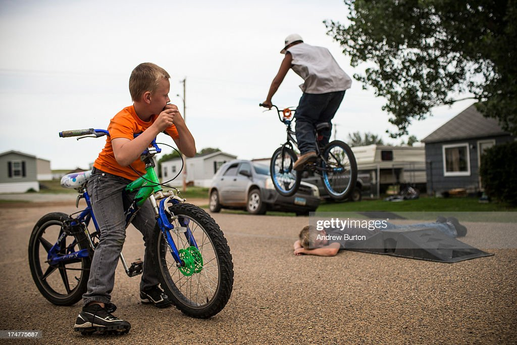 Jerome (L) watches as Zach (on bike), jumps over Fielding on July 28, 2013 in Alexander, North Dakota. Fielding's dad, who works as a mechanic and welder, moved the family to North Dakota from Mexico after learning of work being offered. North Dakota has been experiencing an oil boom in recent years, due in part to new drilling techniques including hydraulic fracturing and horizontal drilling. In April 2013, The United States Geological Survey released a new study estimating the Bakken formation and surrounding oil fields could yield up to 7.4 billion barrels of oil, doubling their estimate of 2008, which was stated at 3.65 billion barrels of oil.