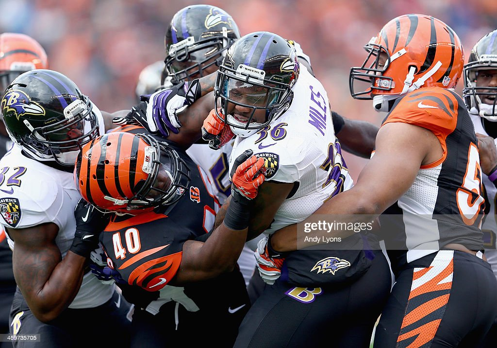 Jeromy Miles #36 of the Baltimore Ravens and Shawn Williams #40 of the Cincinnati Bengals tussle after a play during the 34-17 Bengals win at Paul Brown Stadium on December 29, 2013 in Cincinnati, Ohio.