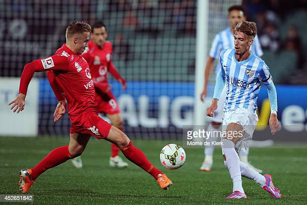 Jeronimo Neumann of Adelaide competes for the ball with Samu Castillejo of Malaga during the international club friendly match between Adelaide...