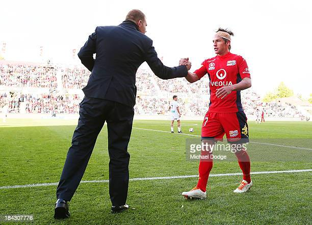 Jeronimo Neumann of United shakes hands with coach Josep Gombau after leaving the field during the round one ALeague match between Perth Glory and...