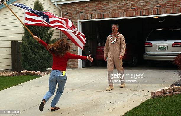 NEIGHBOR Jerri Churchill runs with her American flag to greet her neighbor Lieutenant Colonel Pete Byrne who had just returned to his Parker home...