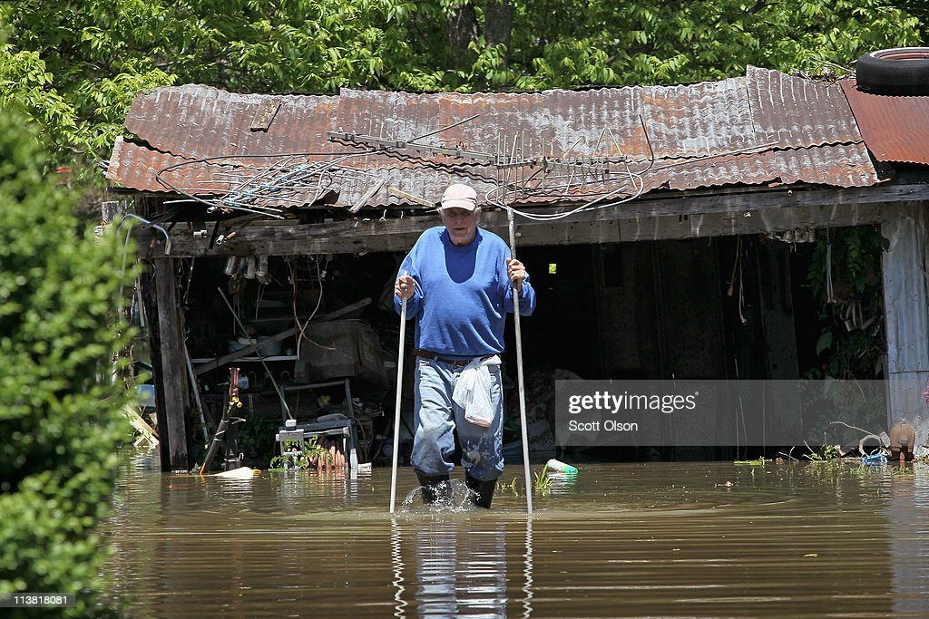 Jerry Brooks uses walking sticks to help him navigate as he wades through his yard May 6, 2011 in Bogota, Tennessee. Heavy rains have left the ground saturated, rivers swollen, and have caused widespread flooding in Missouri, Illinois, Kentucky, Tennessee, and Arkansas.