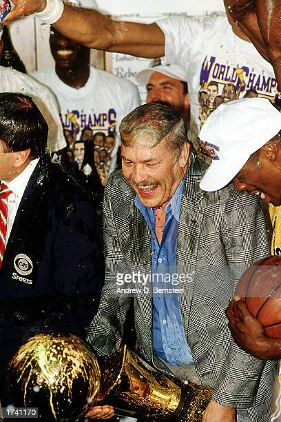 Jerry Buss owner of the Los Angeles Lakers celebrates with the Lakers while holding the Championship Trophy in the lockerroom after winning the 1986...