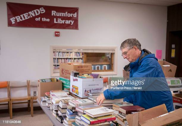 Jerry Cohen arranges books that will be displayed for a benefit book sale at the Rumford Public Library on Thursday, June 13, 2019. Librarians have...