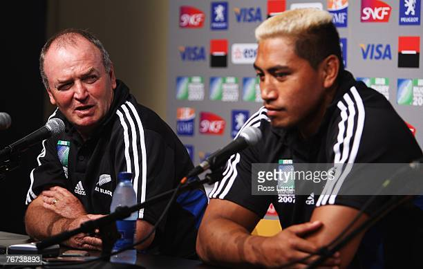 Jerry Collins of the New Zealand All Blacks and head coach Graham Henry talk at a press conference following the captains run at Stade de Gerland on...