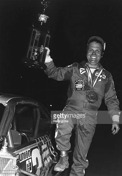 Jerry Cook driver of the Ford Pinto modified hoists one of his many trophies after a NASCAR Modified series race circa 1970's
