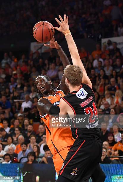 Jerry Evans Jr of the Taipans passes the ball despite the defence of Jesse Wagstaff of the Wildcats during the round 12 NBL match between the Cairns...