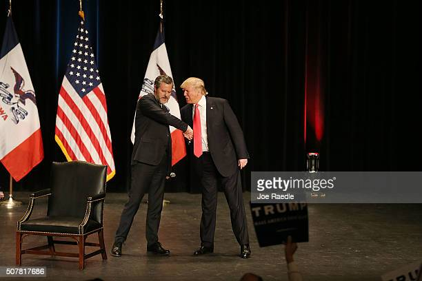 Jerry Falwell Jr greets Republican presidential candidate Donald Trump as he walks on stage during a campaign rally at the Sioux City Orpheum Theatre...