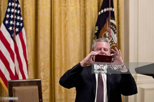 Jerry Falwell Jr president of Liberty University uses a mobile device to take a photograph before an executive order signing event in the East Room...