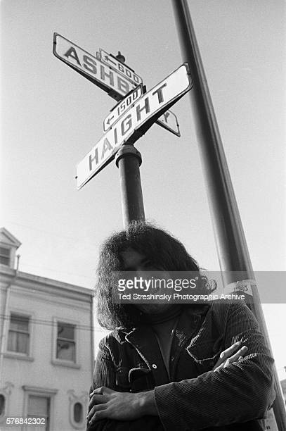 Jerry Garcia of the Greatful Dead stands under the street signs on the corner of Ashbury and Haight streets in San Francisco | Location corner of...