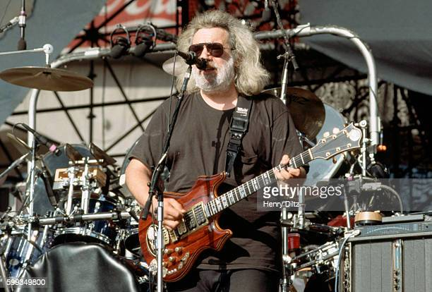 Jerry Garcia plays guitar on stage with his band the Grateful Dead