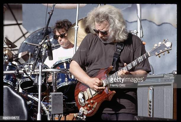 Jerry Garcia plays guitar on stage with his band the Grateful Dead Drummer Mickey Hart plays behind him