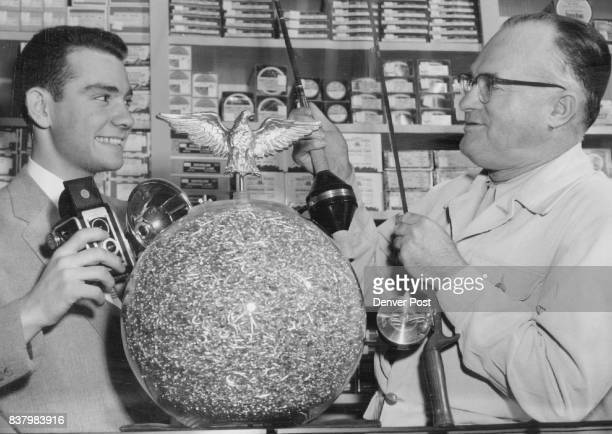 Jerry Gart holds a camera and Jim Haywood holds a spinning rod which will be among prizes that will go to persons who come closest to guessing the...