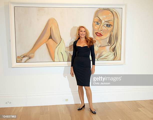 Jerry Hall poses in front of Francesco Clemente's 'Jerry Hall' at Sothebys on October 7 2010 in London England Selected artworks from Jerry Hall's...