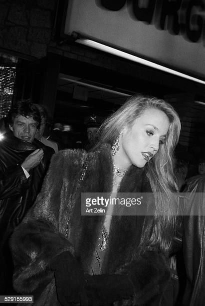 Jerry Hall wearing a fur with Mick Jagger in the background; circa 1970; New York.