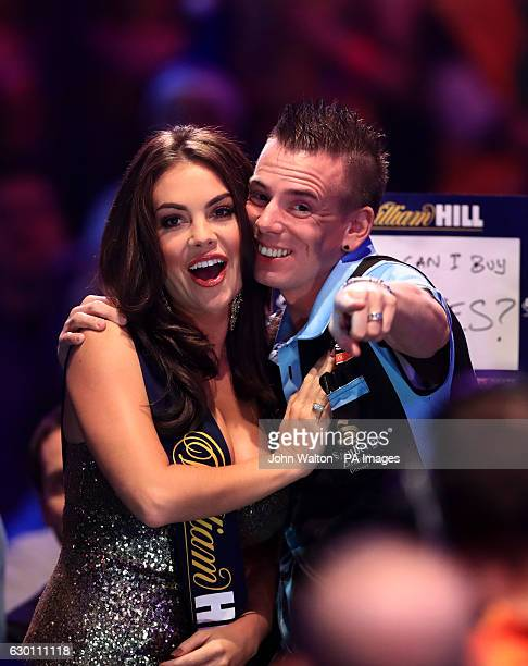 Jerry Hendriks shares a joke with the William Hill walk on girl before the start of his match against Peter Wright during day two of the William Hill...