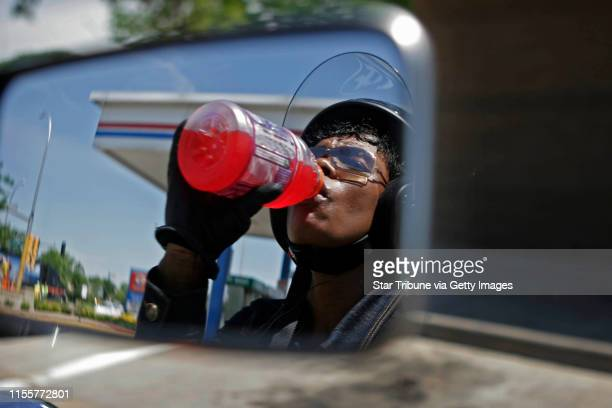 Jerry Holt/Star Tribune 6/22/2005 Brooklyn ParkCharlene Williams who is reflected in the mirrors of her motorcycle cools off with a soft drink after...