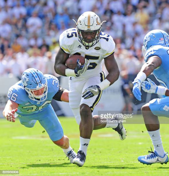 Jerry Howard of the Georgia Tech Yellow Jackets carries the ball against J K Britt and Cole Holcomb of the North Carolina Tar Heels on September 30...