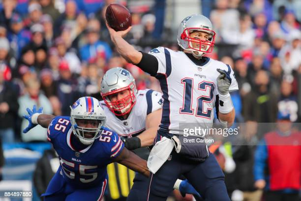 Jerry Hughes of the Buffalo Bills attempts to sack Tom Brady of the New England Patriots as he throws the ball during the first quarter on December 3...