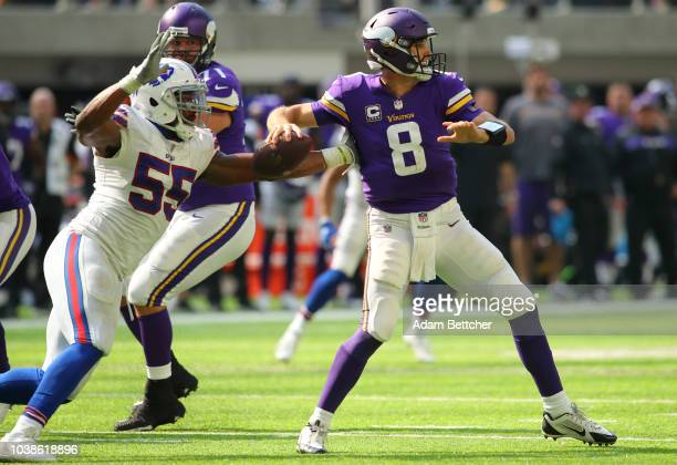 Jerry Hughes of the Buffalo Bills pursues Kirk Cousins of the Minnesota Vikings as he passes the ball in the third quarter of the game at US Bank...