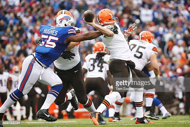 Jerry Hughes of the Buffalo Bills reaches in on quarterback Brian Hoyer of the Cleveland Browns during the first half at Ralph Wilson Stadium on...