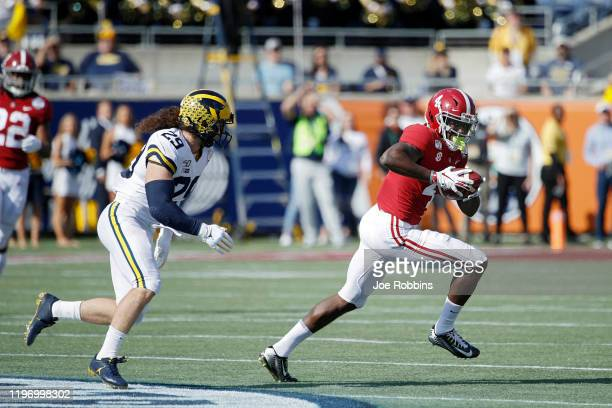 Jerry Jeudy of the Alabama Crimson Tide runs after catching a pass against Jordan Glasgow of the Michigan Wolverines in the first quarter of the Vrbo...