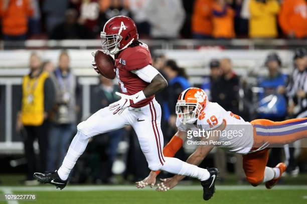Jerry Jeudy of the Alabama Crimson Tide scores a first quarter touchdown reception past Tanner Muse of the Clemson Tigers in the CFP National...
