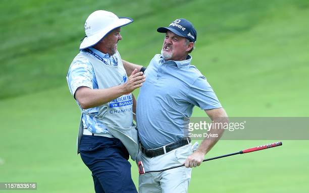 Jerry Kelly celebrates with his caddie after winning the American Family Insurance Championship in sudden death at the University Ridge Golf Course...