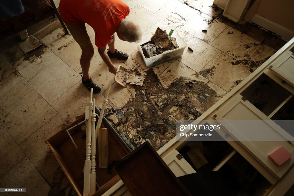 Jerry King uses a dustpan to scrape mud off of his floors