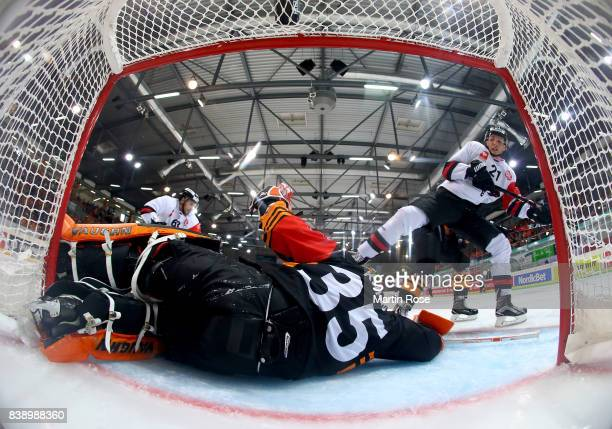 Jerry Kuhn goaltender of Wolfsburg makes a save on Gilbert Gabor of Bystrica during the Champions Hockey League match between Grizzlys Wolfsburg and...