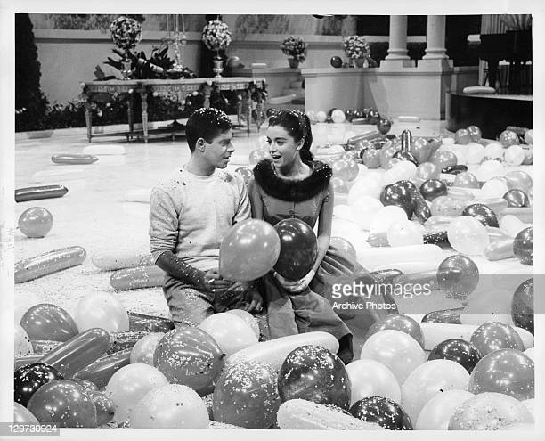 Jerry Lewis and Anna Maria Alberghett on the floor with balloons in a scene from the film 'Cinderfella' 1960