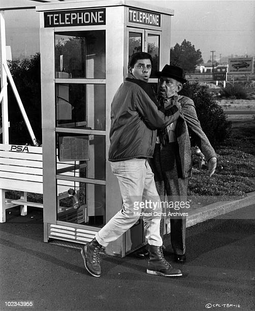 Jerry Lewis grabs another actor by his lapels outside a telephone booth in a scene from the movie The Big Mouth which was released July 12 1967