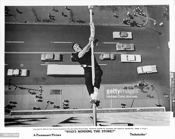 Jerry Lewis hanging from flagpole in a scene from the film 'Who's Minding The Store' 1963