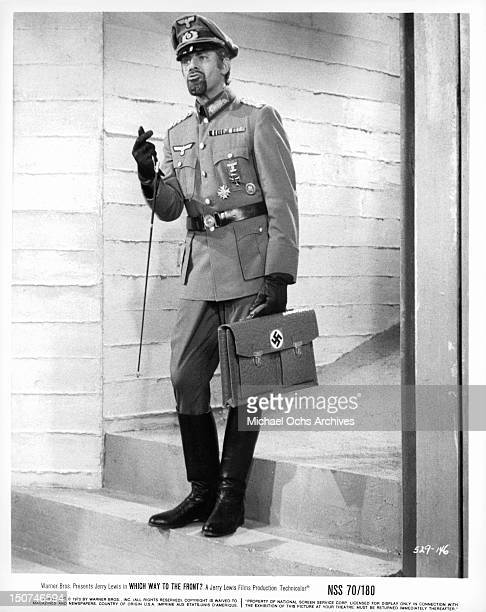 Jerry Lewis in a military uniform carrying a briefcase with a nazi symbol on it in a scene from the film 'Which Way To The Front?', 1970.