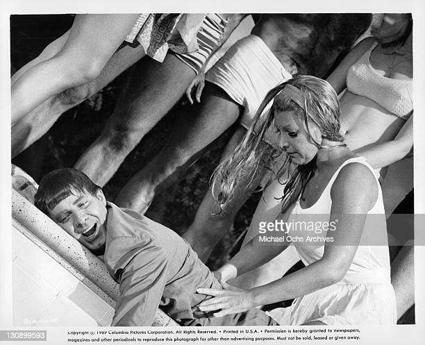 Jerry Lewis is tended to by blonde by the pool in a scene from the film 'Hook Line and Sinker' 1969