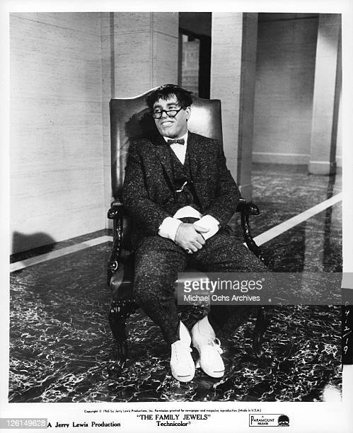Jerry Lewis sitting in a chair with glasses bow tie and buck teeth in a scene from the film 'The Family Jewels' 1965