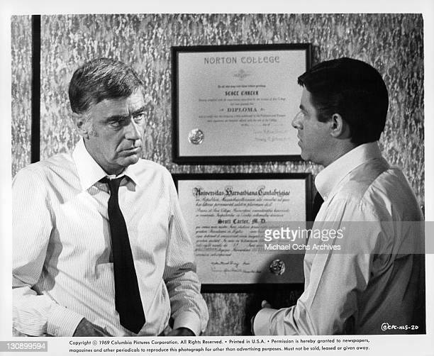 Jerry Lewis speaks to Peter Lawford in his office in a scene from the film 'Hook Line and Sinker' 1969