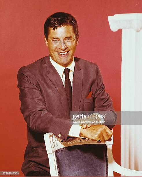 Jerry Lewis US comedian and actor wearing a grey jacket white shirt and black tie and smiling in a studio portrait against a red background circa 1965