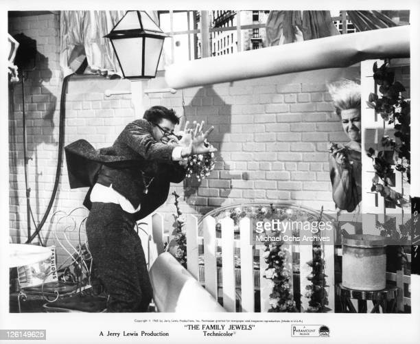 Jerry Lewis with glasses bow tie and buck teeth holding a bouquet of flowers in a panic in a scene from the film 'The Family Jewels' 1965
