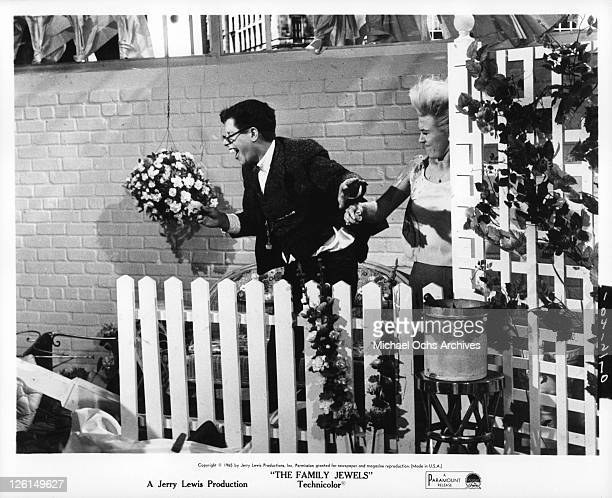 Jerry Lewis with glasses bow tie and buck teeth holding a bouquet of flowers in a scene from the film 'The Family Jewels' 1965