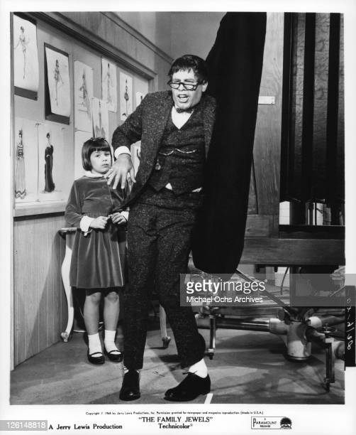 Jerry Lewis with the glasses bow tie and buck teeth stands pigeon toed while Donna Butterworth stands behind him in a scene from the film 'The Family...