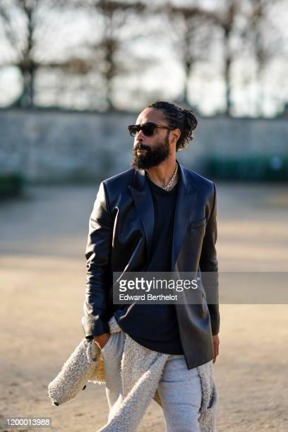 Jerry Lorenzo Founder of Fear of God wears a black leather jacket a tshirt white pants shoes sunglasses outside Vuitton during Paris Fashion Week...